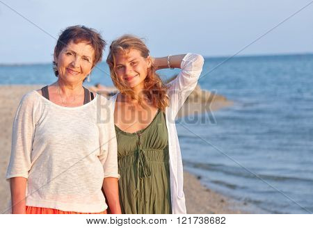 mother and adult daughter on sea shore, family portrait