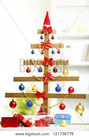 A handmade Christmas tree and presents on the table, in the room