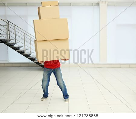 Man holding pile of carton boxes in the room