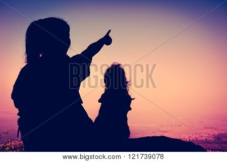 Silhouette Back View Of Mother And Child Hikers Enjoying The View At The Top Of A Mountain. Cross Pr