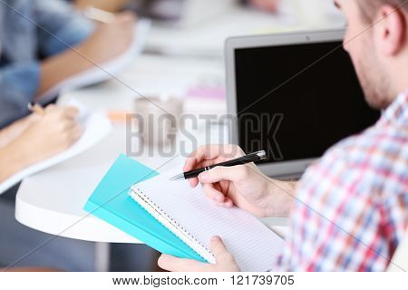 Young man sitting and making notes at the office meeting