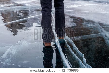 Woman walking on blue cracked ice of frozen lake Baikal.  Ice with reflection.