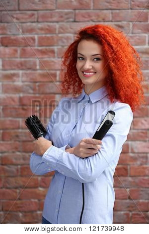 Red haired beautiful girl with comb and hair iron