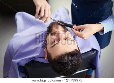 Professional hairdresser cutting beard with scissors