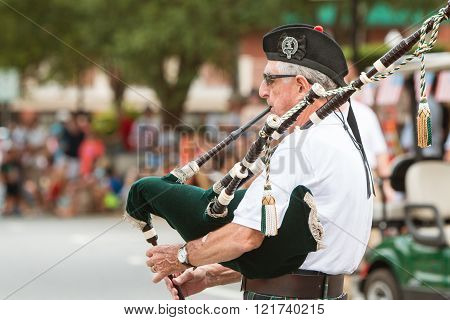ALPHARETTA, GA - AUGUST 2015:  A senior man plays the bagpipes before the start of the annual Old Soldiers Day Parade in Alpharetta GA on August 1 2015.