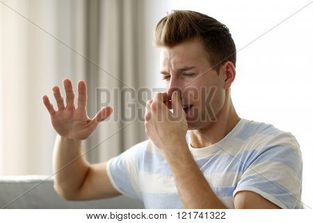 Young blonde man pinching his nose because of the stench in the room