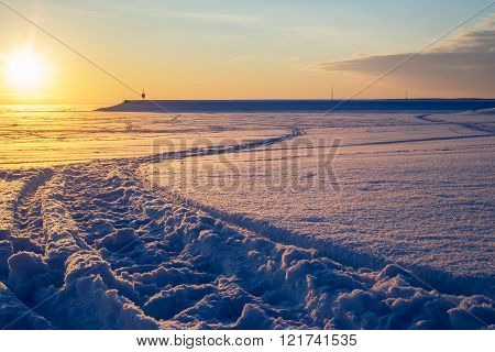 Cross country ski trace towards pier at sunset. Beautiful winter scene