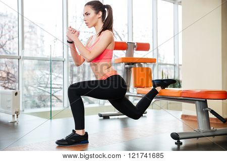 Pretty concentrated young sportswoman doing squats using bench in gym