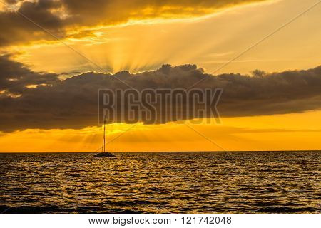 Beautiful scenic warm sunset at the beach in kiehi Maui Hawaii. Golden light of ray of sun covered by clouds