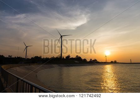 power generator wind turbines at sunset with reservoir