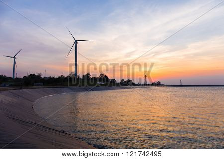 power generator wind turbines at twilight time with reservoir