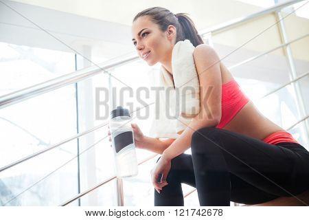 Happy beautiful young sportswoman resting and drinking water on stairs in gym