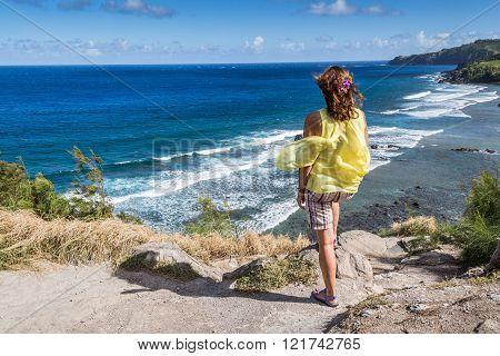 Female tourist admiring the beautiful Hawaiian coastline in Maui. Beautiful blue waters and sky