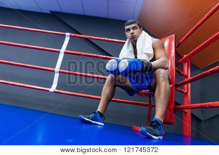 Male boxer with towel sitting in the corner of the boxing ring
