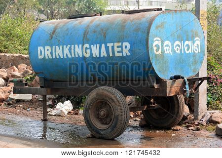 GOLPALPUR, ORISSA STATE, INDIA - FEBRUARY 1, 2014: Mobile water tanker at town's roadside is bright blue and easy to spot by villagers when water is delivered.  English and Indian text shows clean drinking water is for public use.  A short hose hangs from