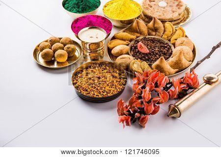 holi festival food with colours, indian festival holi, samosa, kachori, laddu, gujiya, palash flower