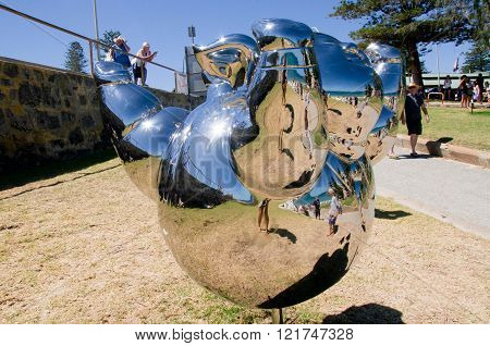 COTTESLOE,WA,AUSTRALIA-MARCH 12,2016: Mirrored Figure Sculpture on the Cottesloe Beach foreshore and people at the arts festival Sculptures By The Sea in Cottesloe, Western Australia.