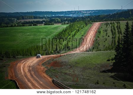 Car moving on the unpaved road on hilly summer terrain