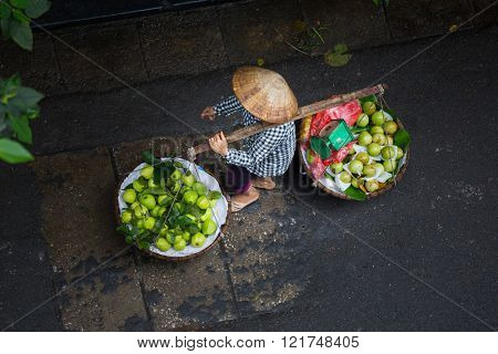 A man carry two baskets with fruits on the yoke, Vietnam