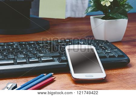 White smartphone on wooden table