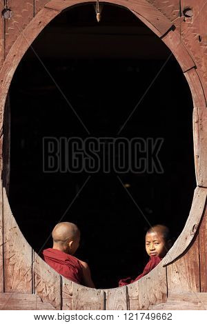 NYAUNG SHWE, MYANMAR, JANUARY 27, 2015: Two young novice buddhist monk are talking at a window of the Shwe Yaunghwe Kyaung monastery in Nyaung Shwe, Myanmar (Burma).