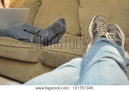 The legs of a couple relaxing on a sectional couch looking at their laptops. A casual occasion as evidenced by worn-out socks covered in cat hair and worn-out sneakers.