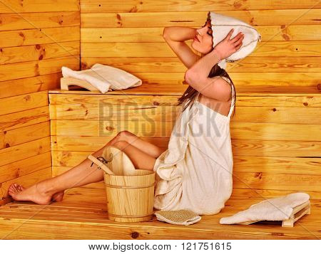 Woman in sauna hat  relaxing at sauna. Girl sitting on sauna wooden boards.