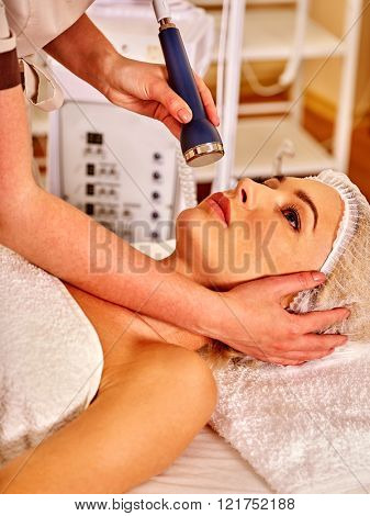 poster of Head of young woman receiving electric ultrusound facial massage at beauty salon. Anti- aging facial massage.