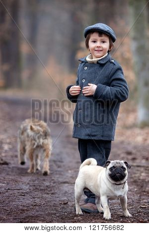 Cute little child, preschool boy, playing with little pet dog in the forest