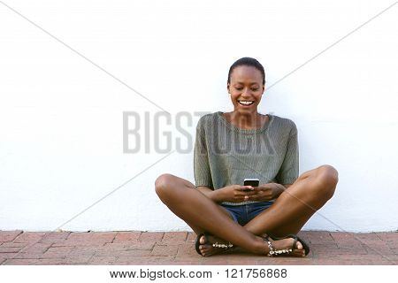 Happy Young Woman Sitting On Sidewalk With Cell Hone
