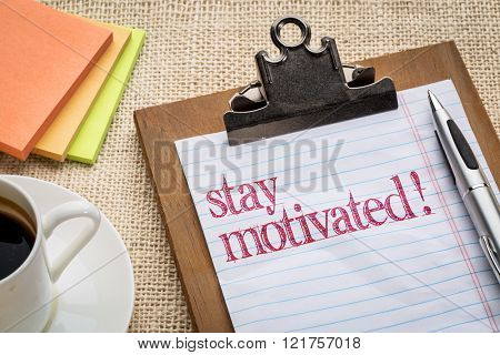 Stay motivated  - motivational advice or reminder on a clipboard with a cup of coffee