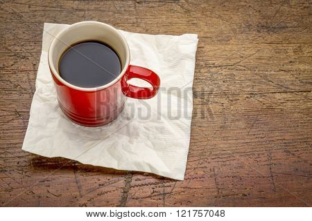 red stoneware cup of espresso coffee with a napkin on a rustic wood