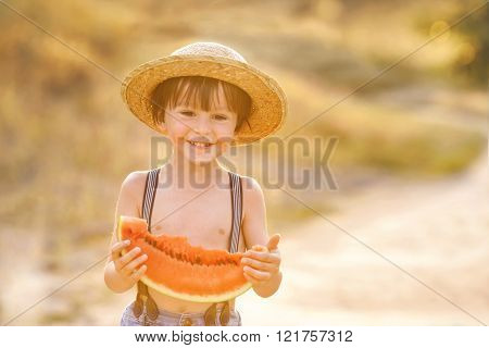 Beautiful little happy child, boy, eating big slice of watermelon, summertime outdoor on sunset