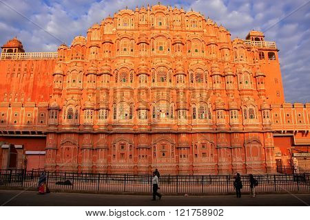 JAIPUR, INDIA - MARCH 3: Unidentified people walk near Hawa Mahal on March 3, 2011 in Jaipur, India. Hawa Mahal was designed by Lal Chand Ustad in the form of the crown of Krishna.