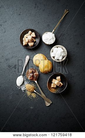 Assorted types of sugar on a stone background
