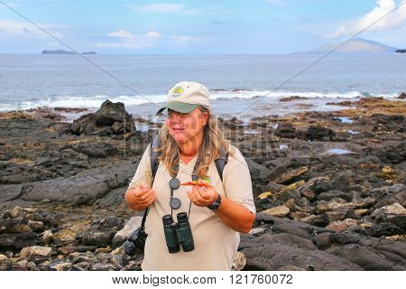 Galapagos, Ecuador - April 20: Unidentified Woman Naturalist Shows Sally Lightfoot Crab Shell On Apr