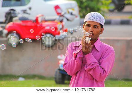 JAIPUR INDIA - NOVEMBER 13: Unidentified man makes soap bubbles at Man Sagar Lake waterfront on November 13 2014 in Jaipur India. Jaipur is the capital and the largest city of Rajasthan