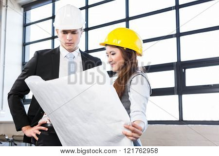 Architects looking at blueprint in office