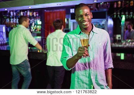 Man posing with glass of beer and friends at bar counter in background