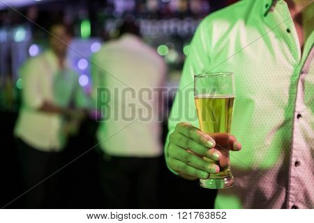 Man posing with glass of beer in bar
