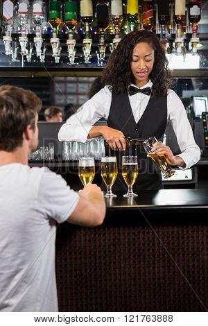 Beautiful barmaid serving beer at bar counter in bar