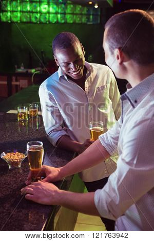 Two men having beer at bar counter in bar