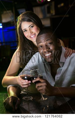 Portrait of couple smiling and toasting their wine glasses at bar counter in bar