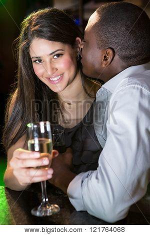 Man kissing woman at bar counter in bar