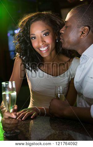 Man kissing a woman while having champagne at bar counter in bar