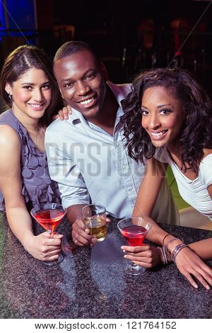 Portrait of young friends having drinks at bar counter in bar