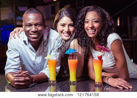 Portrait of friends enjoying while having cocktail drinks at bar counter in bar