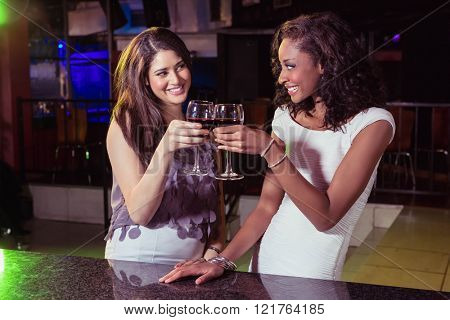 Young women toasting wine glasses at bar counter in bar