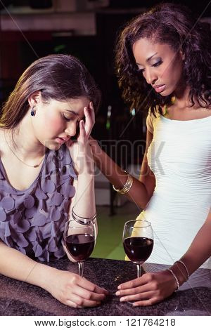 Woman having drinks and comforting her depressed friend in bar