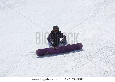 Young Snowboarder Woman Sitting On The Ski Slope.